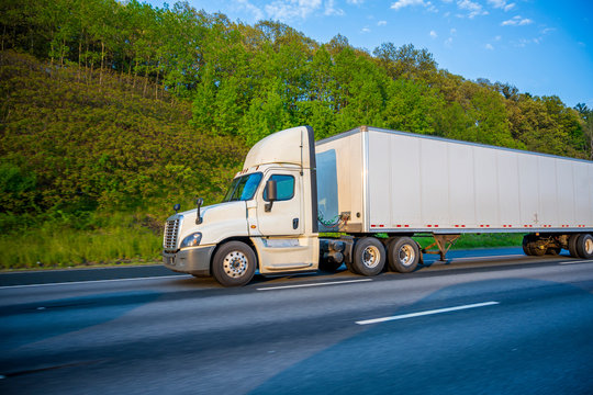 Big rig white day cab semi truck with roof spoiler transporting commercial cargo in dry van semi trailer running on the road with green hill