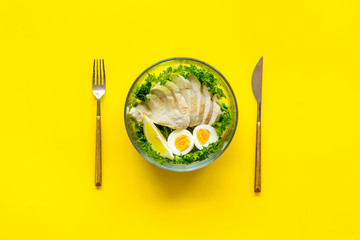 meal in bowl to take away on yellow background top view