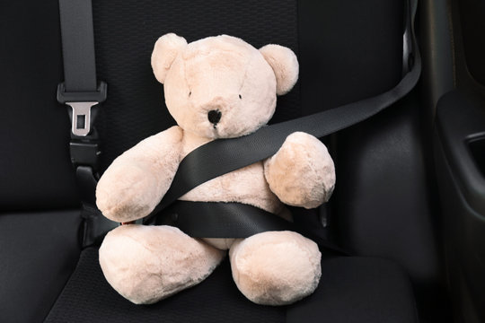 Child's toy bear buckled with safety belt on car backseat. Prevention of danger