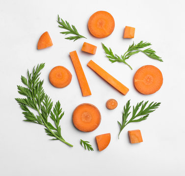 Cut carrot and leaves isolated on white, top view