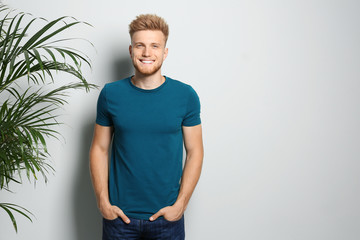 Young man wearing blank t-shirt on light background. Mockup for design
