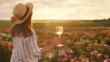 Woman with glass of wine in rose garden on sunny day. Space for text