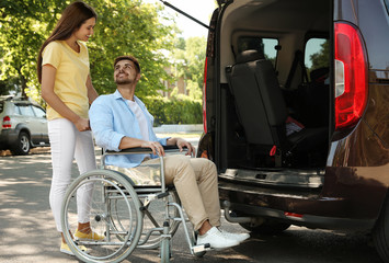 Young woman helping man in wheelchair to get into van outdoors Fototapete