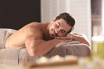 Handsome young man relaxing on massage table in spa salon
