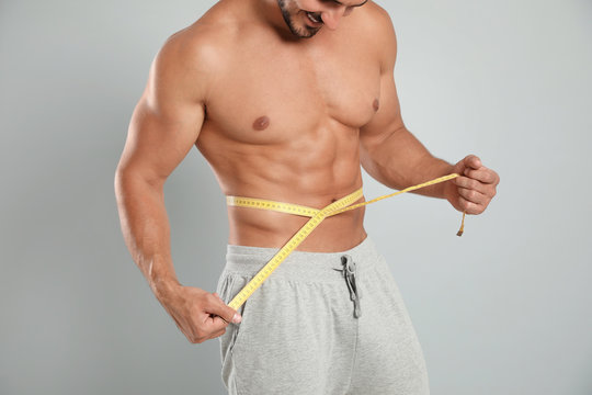 Young man with slim body using measuring tape on grey background, closeup view