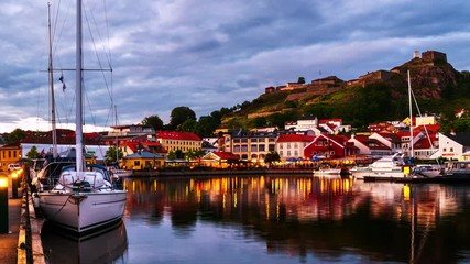 Wall Mural - Halden, Norway. View of the illuminated houses and yachts with Fredriksted fortress at the background. Time-lapse at sunset with cloudy sky in summer, panning video