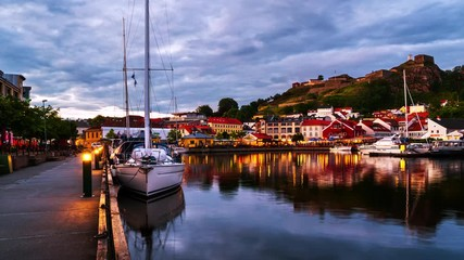 Wall Mural - Halden, Norway. View of the illuminated houses and yachts with Fredriksted fortress at the background. Time-lapse at sunset with cloudy sky in summer, zoom in