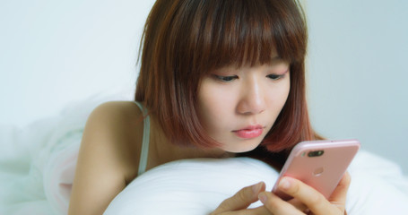 Woman Use Phone And Smile Happily On The Bed