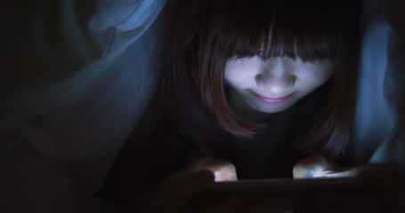 Woman Use Phone On The Bed at night