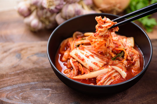 Eating kimchi cabbage in a bowl with chopsticks, Korean food