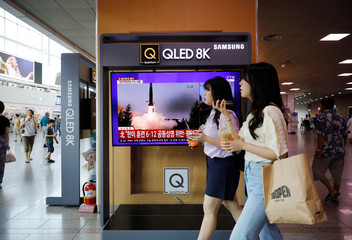 Women walk past a TV showing a file picture for a news report on North Korea firing two unidentified projectiles, in Seoul