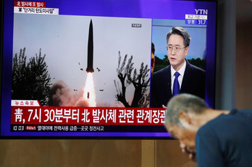 A man watches a TV showing a file picture for a news report on North Korea firing two unidentified projectiles, in Seoul