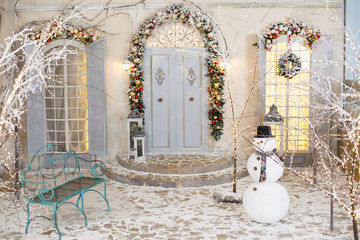 Decorative snowman on background of Christmas fecorated house. Studio decoration in New Year style. Snow covered courtyard of an old stone house