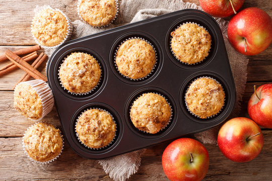 Rustic style fresh apple muffins with cinnamon close-up on the table. Horizontal top view