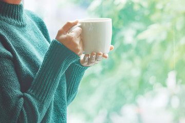 Women wearing green sweaters in their hands holding a white coffee cup in a relaxed mood at the...
