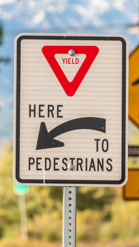 Vertical Yield Here To Pedestrians sign against trees and mountain viewed on a sunny day