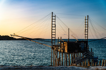 Beautiful seascape with a view of a trabucco at sunset in Italy