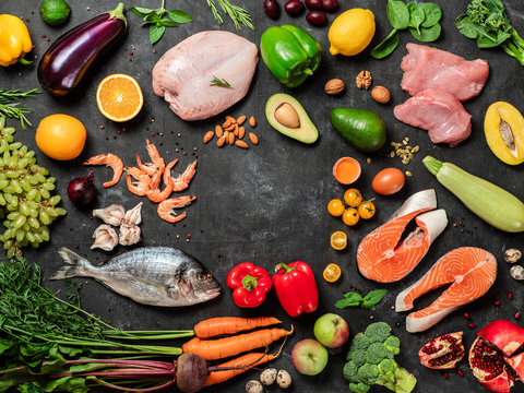 Paleo diet concept with copy space in center. Raw ingredients for Paleo diet - fish, seafood, poultry meat, vegetables and fruits on dark background. Top view or flat lay.