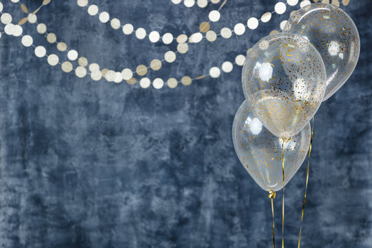 Three balloons with confetti and gold garlands on a smoky dark blue background. Birthday and holiday decor.