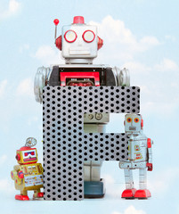 Fototapete - retro robots holding a big  metal letter F with blue sky