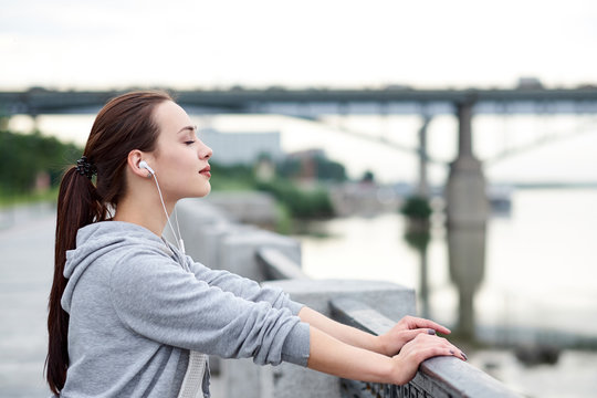 Fitness healthy asian woman runner relaxing after running outdoors enjoying view on waterfront