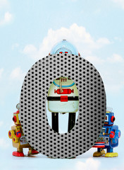 Wall Mural - retro robots holding a big  metal letter O  with blue sky