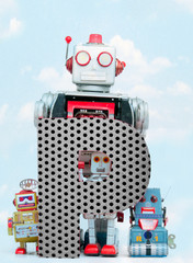 Wall Mural - retro robots holding a big  metal letter P with blue sky