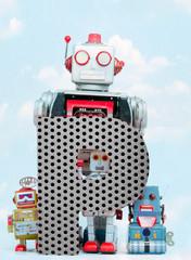 Fototapete - retro robots holding a big  metal letter P with blue sky