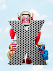 Fototapete - retro robots holding a big  metal letter  X with blue sky