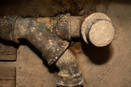 Worn out rusty water pipe in a concrete wall