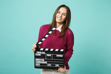 Young brunette woman girl in casual clothes posing isolated on blue green wall background studio portrait. People sincere emotions lifestyle concept. Mock up copy space. hold film making clapperboard.