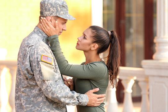 Sad woman saying goodbye to her military husband outdoors