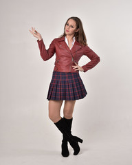 full length portrait of a brunette girl wearing a red leather jacket and plaid skirt, standing pose on a cream studio background.