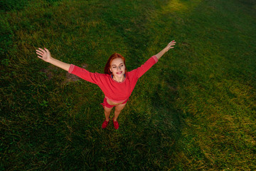 Top view photo of happy healthy sportswoman on the background of green grass