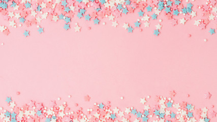 Festive border frame of colorful pastel sprinkles on pink background with copy space in center. Sugar sprinkle dots and stars, decoration for cake and bakery. Top view or flat lay. Banner Fototapete