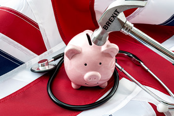 The destroying of the single-payer healthcare in the United Kingdom as result of Brexit and defunding the National Health Service or NHS concept theme with hammer wrecking piggy bank and stethoscope