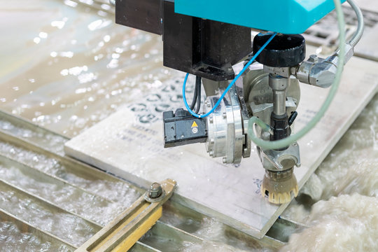 close up nozzle of high speed and precision automatic computer control high pressure water jet cutting machine during manufacturing process cut stone or metal sheet of industrial work