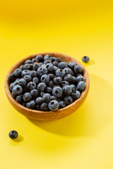 Fresh blueberry in wooden bowl on yellow background