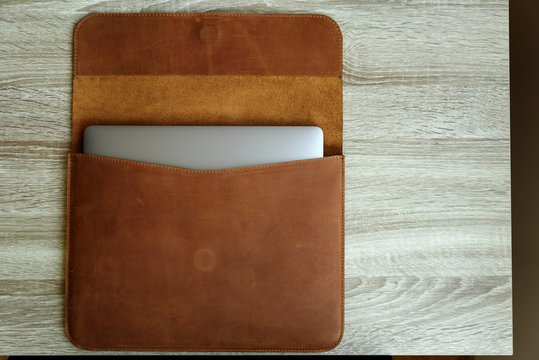 Brown leather case with laptop on wooden table. Top view. Copy space