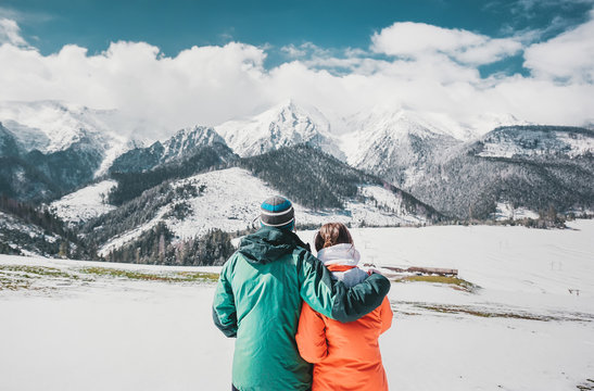 Back view photo of young loving couple hugging over winter mountains. Looking at mountains.