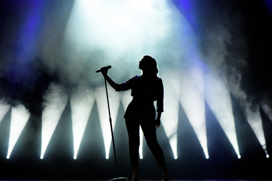 Vocalist singing to microphone. Singer in silhouette