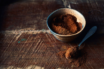 Ground coffee in rustic ceramic cup. Wooden background. Still life
