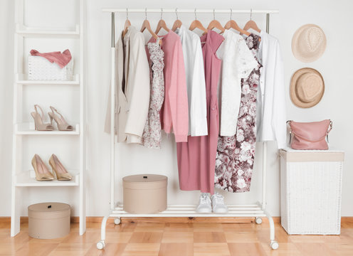 Collection of female clothes hanging on rack in dressing room