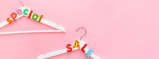 Wall Mural - White hangers with sale text on pink background