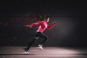 Side motion view of attractive sporty athlete running girl in sportswear at the street in front of...