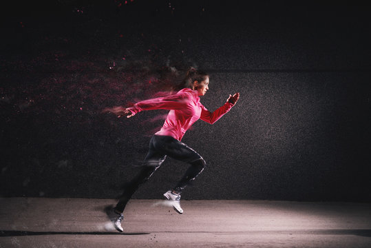 Side motion view of attractive sporty athlete running girl in sportswear at the street in front of the grey wall.