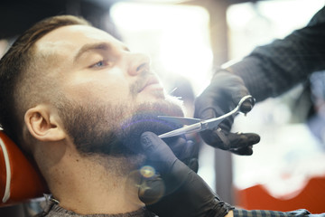 a guy doing a haircut and styling a beard