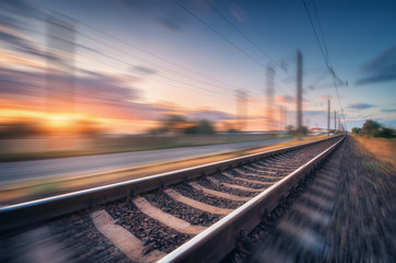 Fototapeten Eisenbahnschienen Railroad and beautiful blue sky with clouds at sunset with motion blur effect in summer. Industrial landscape with railway station and blurred background. Railway platform in speed motion. Concept