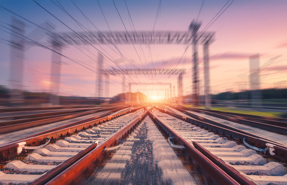 Railroad and pink sky with motion blur effect at sunset. Industrial landscape with railway station, light and blurred background at twilight. Railway platform in move. Transportation. Speed motion