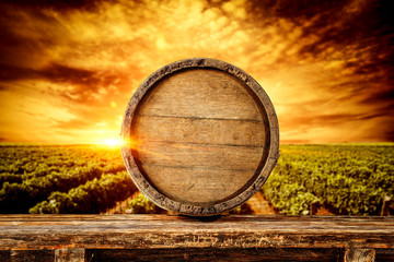 Papiers peints Vignoble wooden old barrel and vineyard backgroundwith sunset time.